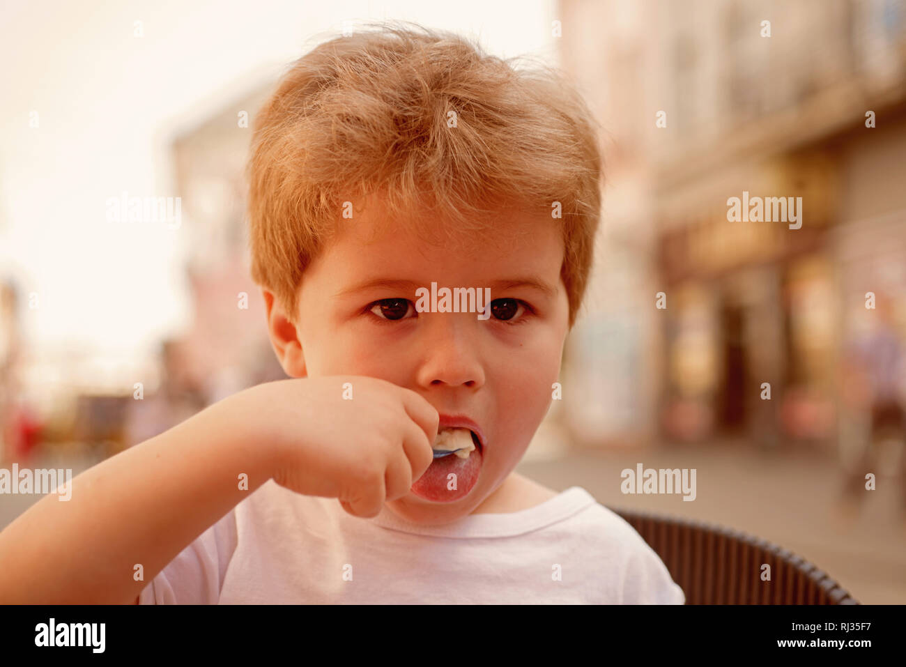 Taking care of a kids hair. Little child eating outdoor. Small boy with stylish haircut. Little child with short blond hair. Healthy hair care habits - Stock Image