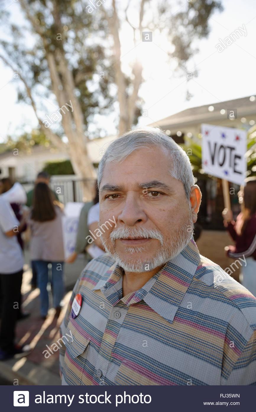 Portrait confident Latinx senior man canvassing voters with neighbors - Stock Image
