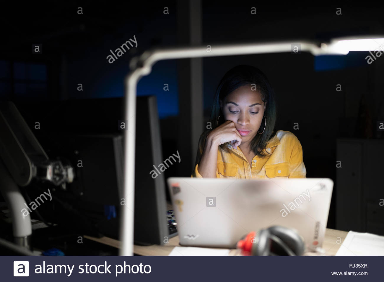 Dedicated businesswoman working at laptop in dark office - Stock Image