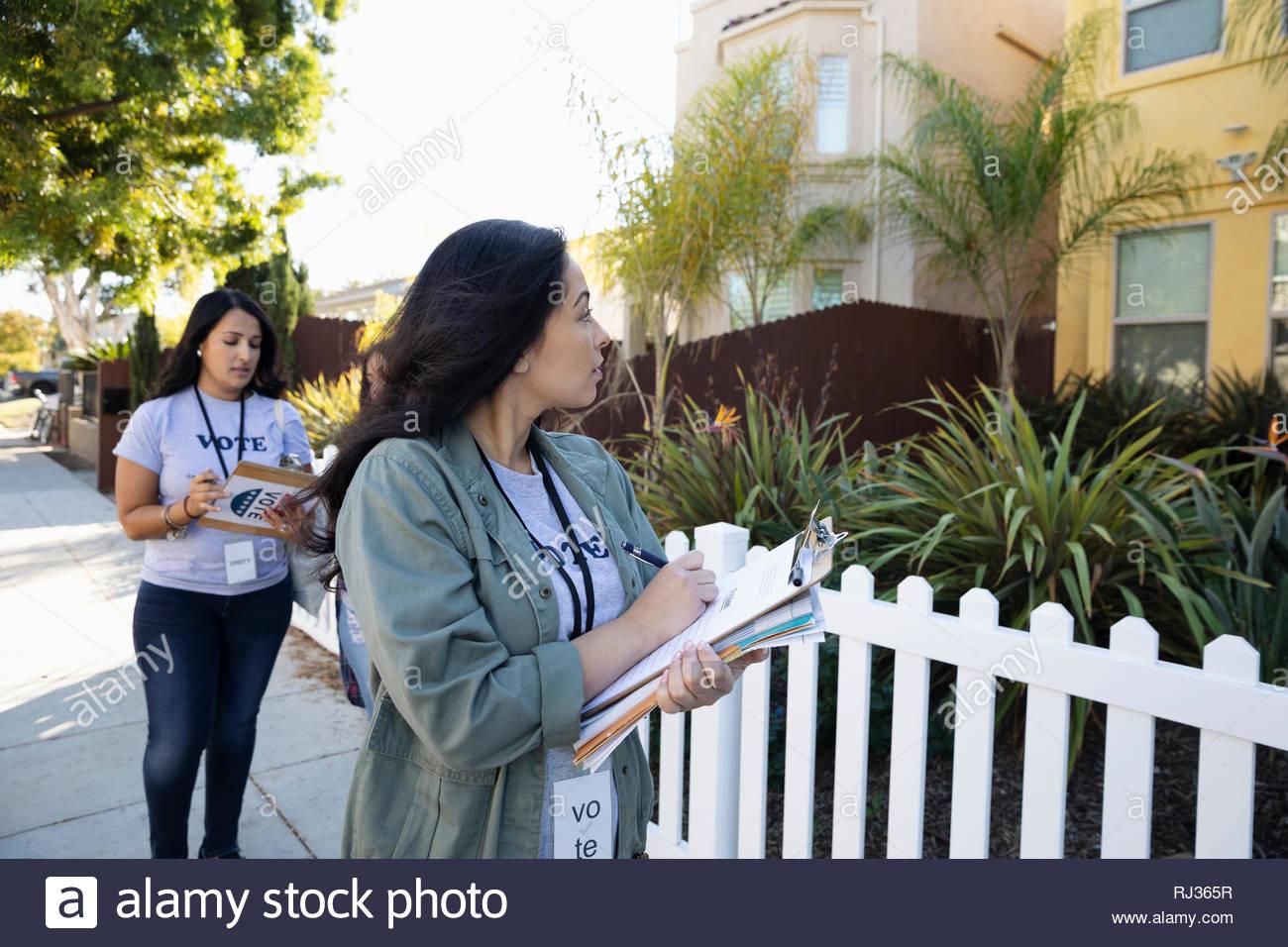 Latinx female volunteers with clipboards volunteering, canvassing voters door-to-door - Stock Image