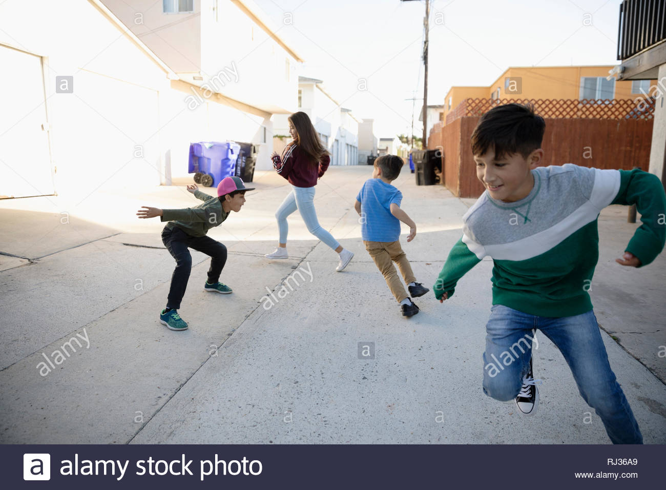 Latinx children playing tag in alley - Stock Image