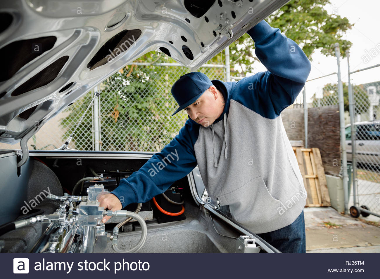 Latinx man checking hydraulics of low rider car in parking lot - Stock Image