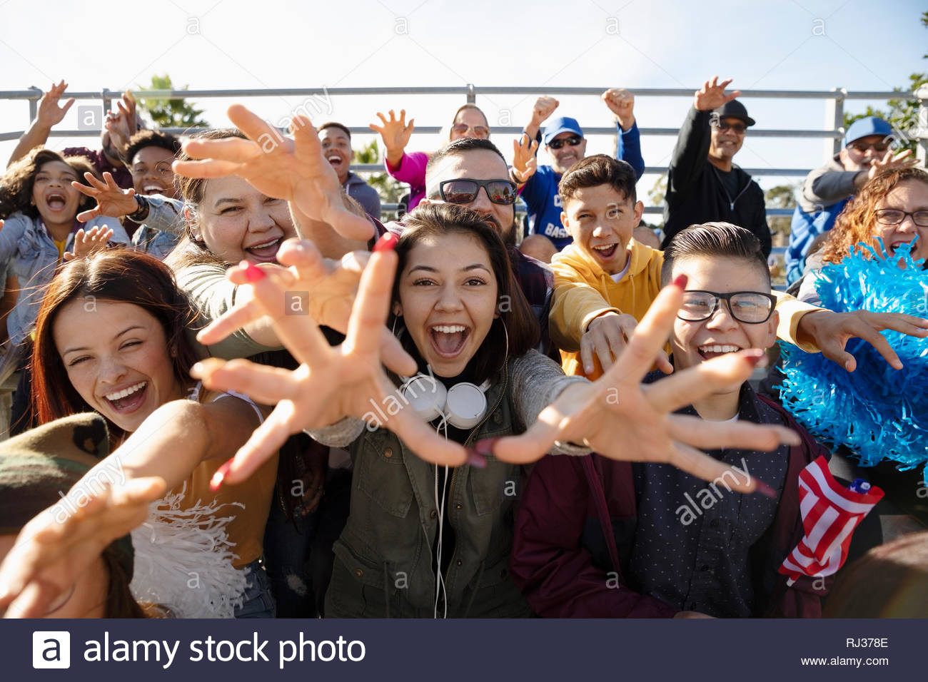 Excited fans cheering from bleachers at baseball game - Stock Image