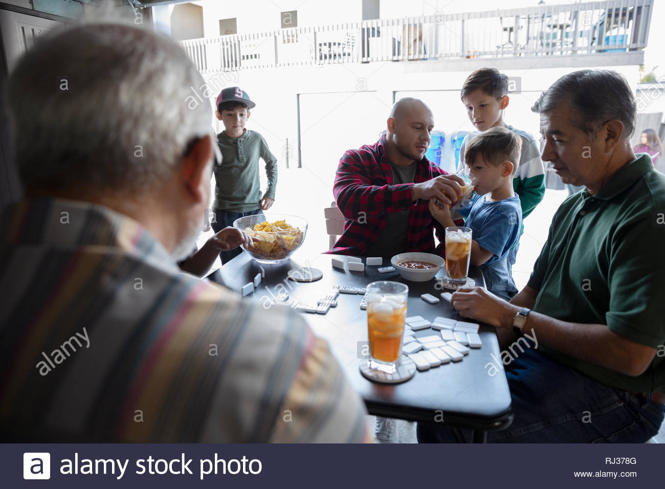 Latinx multi-generation family playing dominos in garage - Stock Image