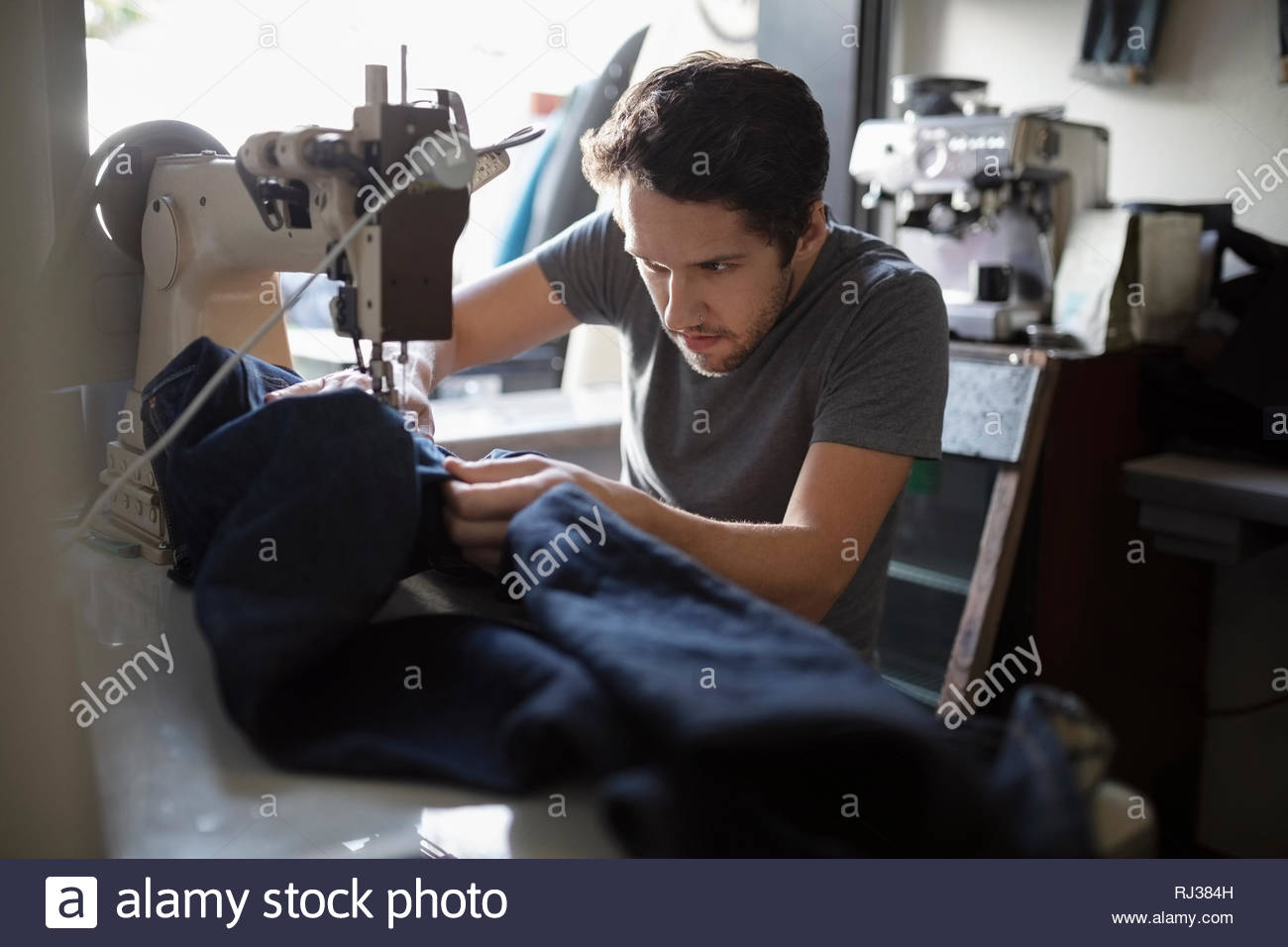 Focused male tailor using sewing machine in denim repair shop - Stock Image