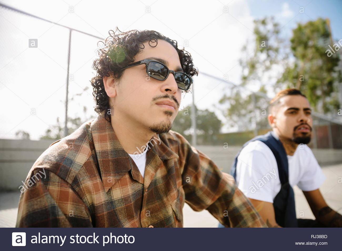 Latinx young men friends hanging out - Stock Image