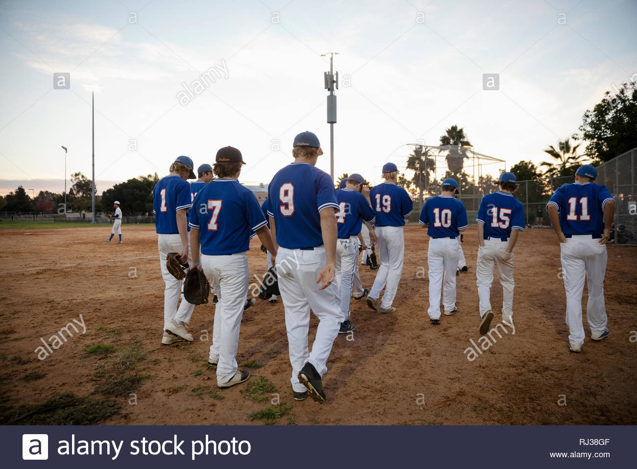 Baseball players walking off field - Stock Image