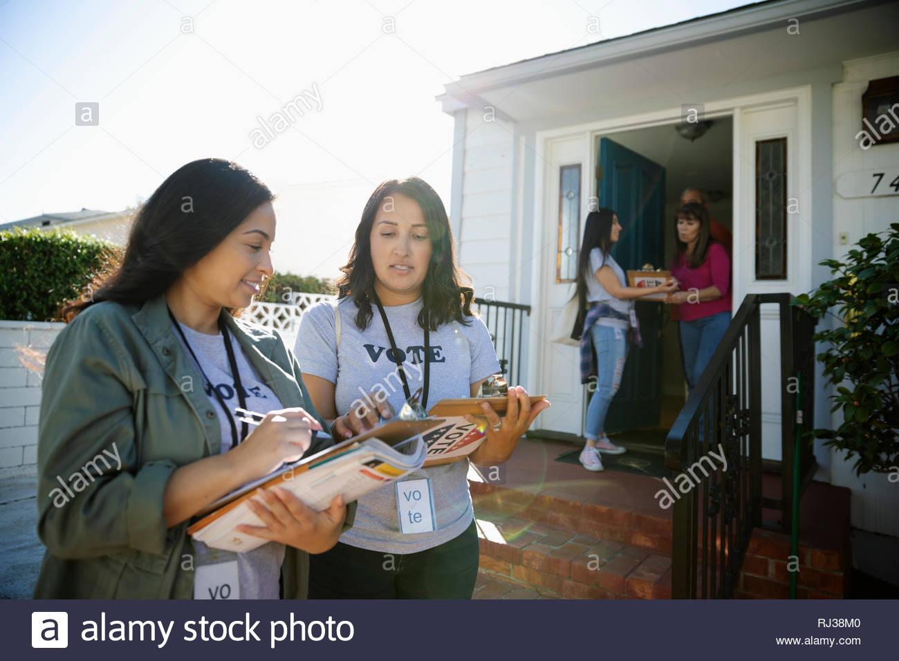 Latinx female volunteers canvassing voters door-to-door - Stock Image