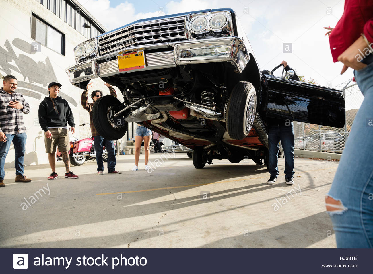 Latinx friends watching low rider car bouncing in sunny parking lot - Stock Image