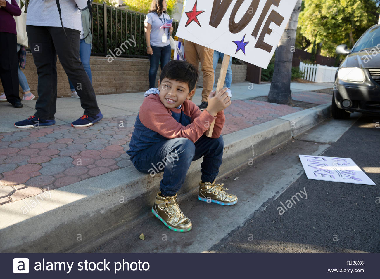 Latinx boy volunteering, canvassing voters on curb - Stock Image