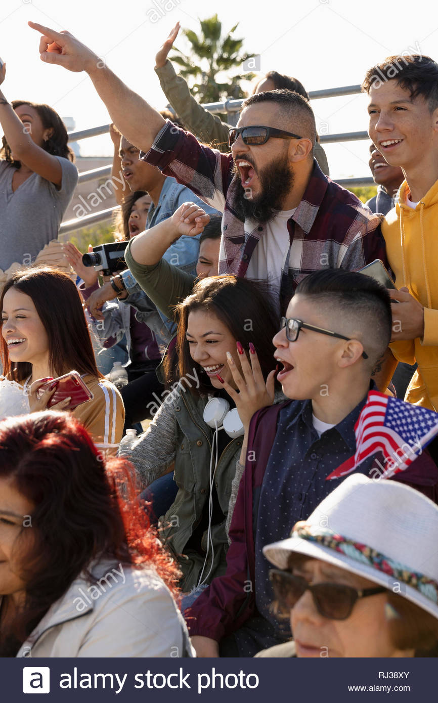 Excited fans cheering in bleachers at baseball game - Stock Image