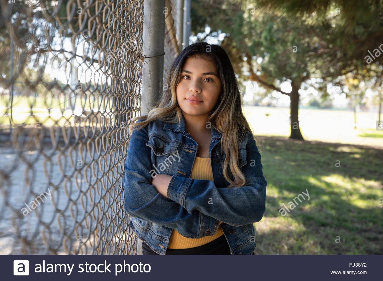 Portrait confident Latinx young woman standing at park fence - Stock Image