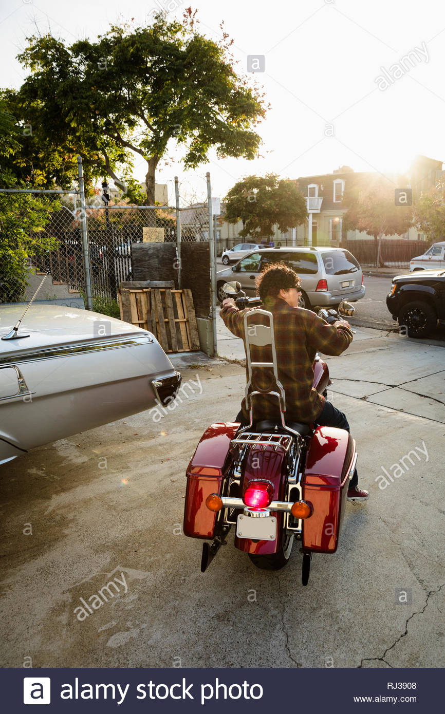 Latinx man driving motorcycle in parking lot - Stock Image