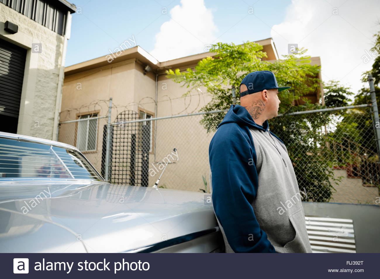 Latinx man leaning against vintage car - Stock Image