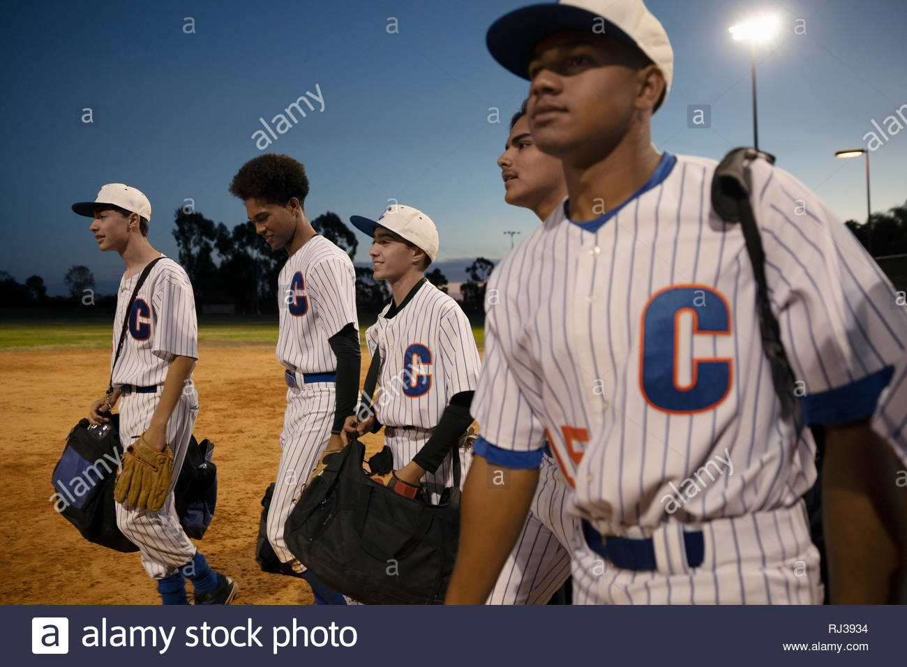 Baseball players walking off field at night - Stock Image