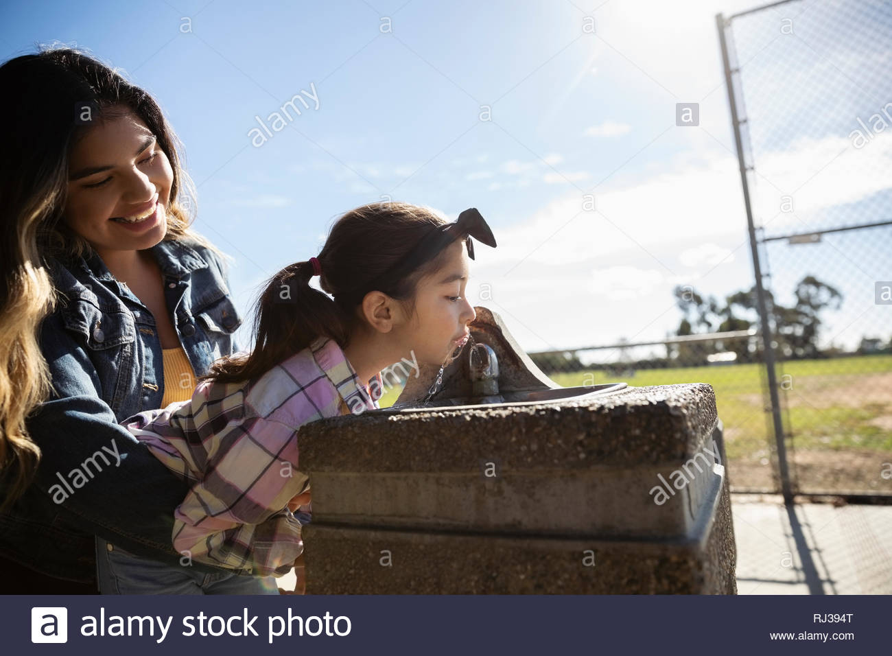 Latinx girl lifting sister to water fountain in sunny park - Stock Image