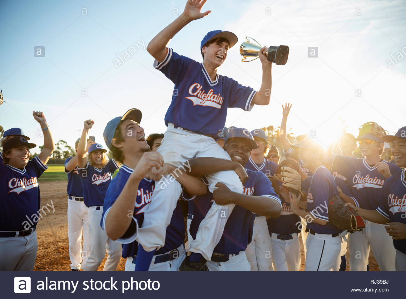 Excited baseball team celebrating, carrying player with trophy on shoulders Stock Photo