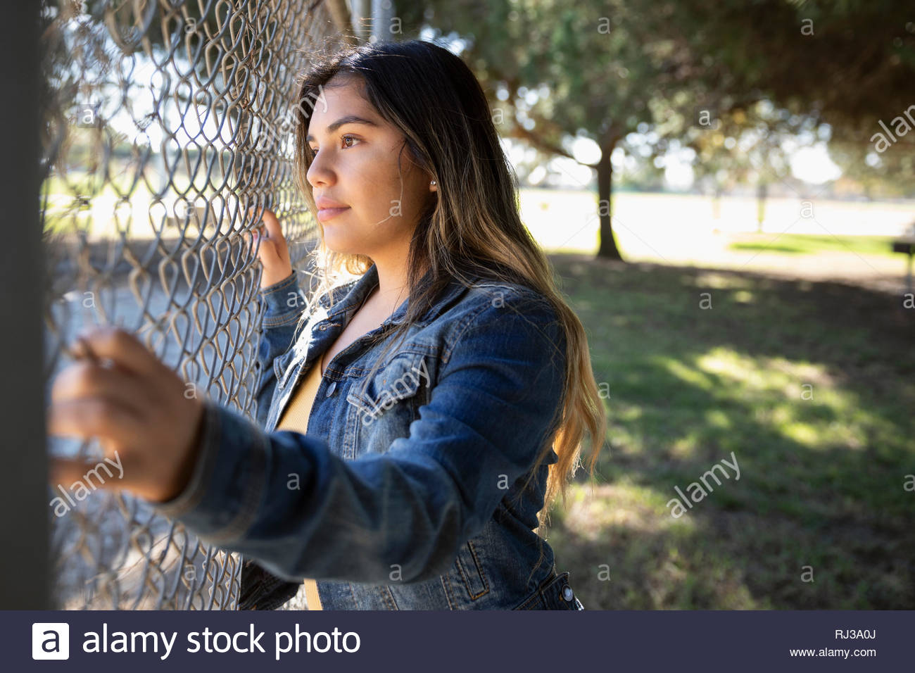 Thoughtful Latinx young woman standing at fence in park - Stock Image