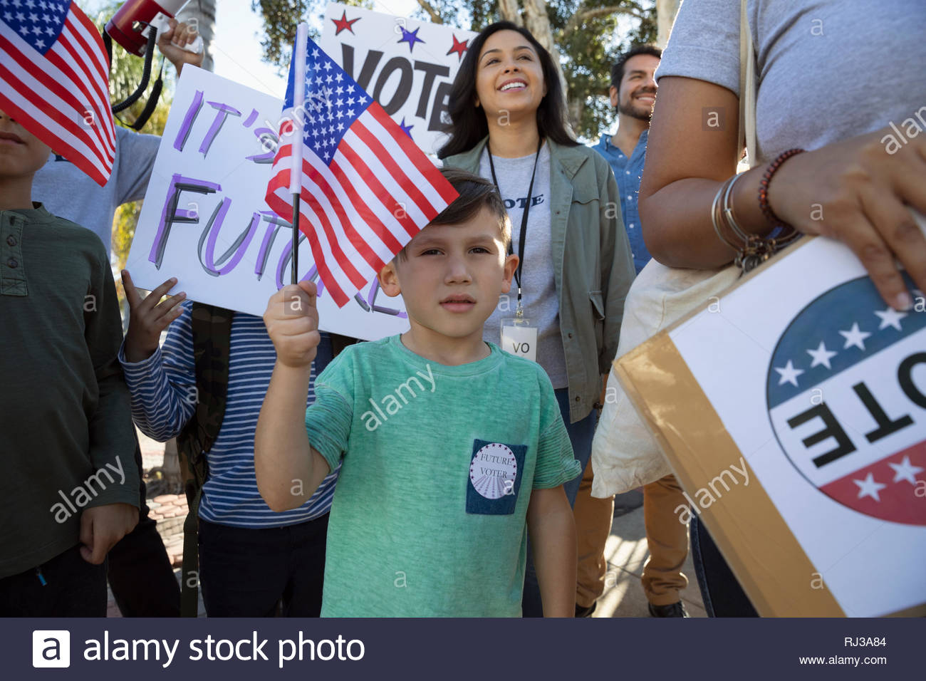 Latinx boy waving American flag, canvassing voters - Stock Image