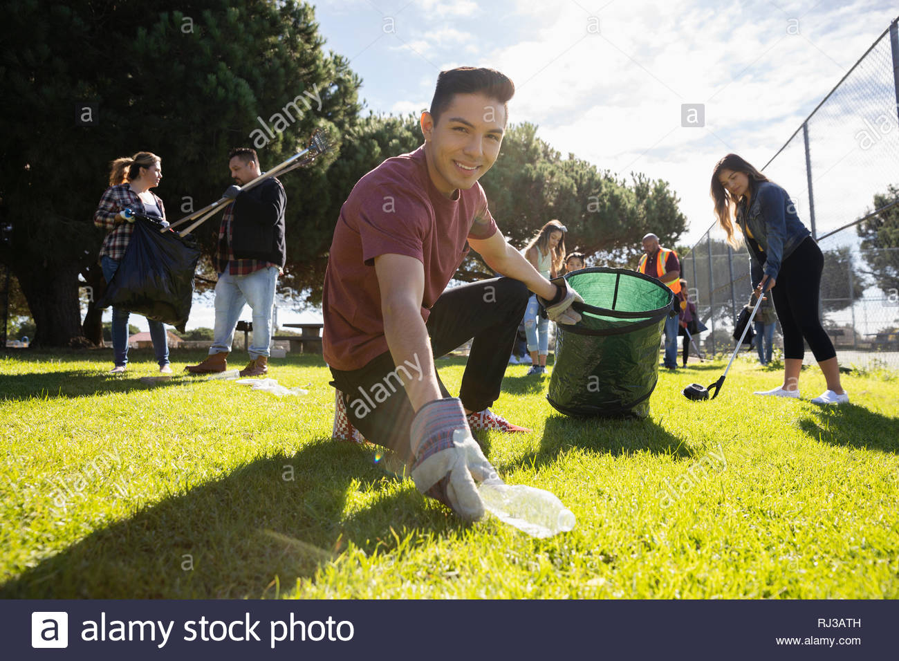 Portrait confident Latinx young male volunteer picking up garbage in sunny park - Stock Image