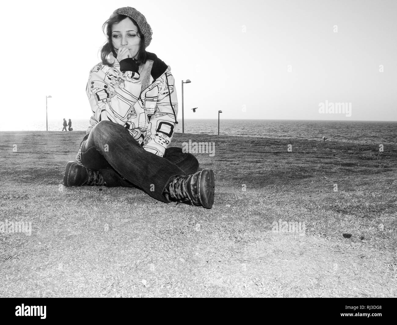 Young girl in casual clothing and urban hat, hoodie and jeans, sitting on grass in a park, over viewing the sea, looking aside in contemplation. - Stock Image