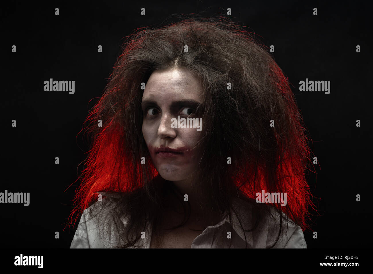 fun crazy young woman with fluffy hair on black background make shy grimace - Stock Image