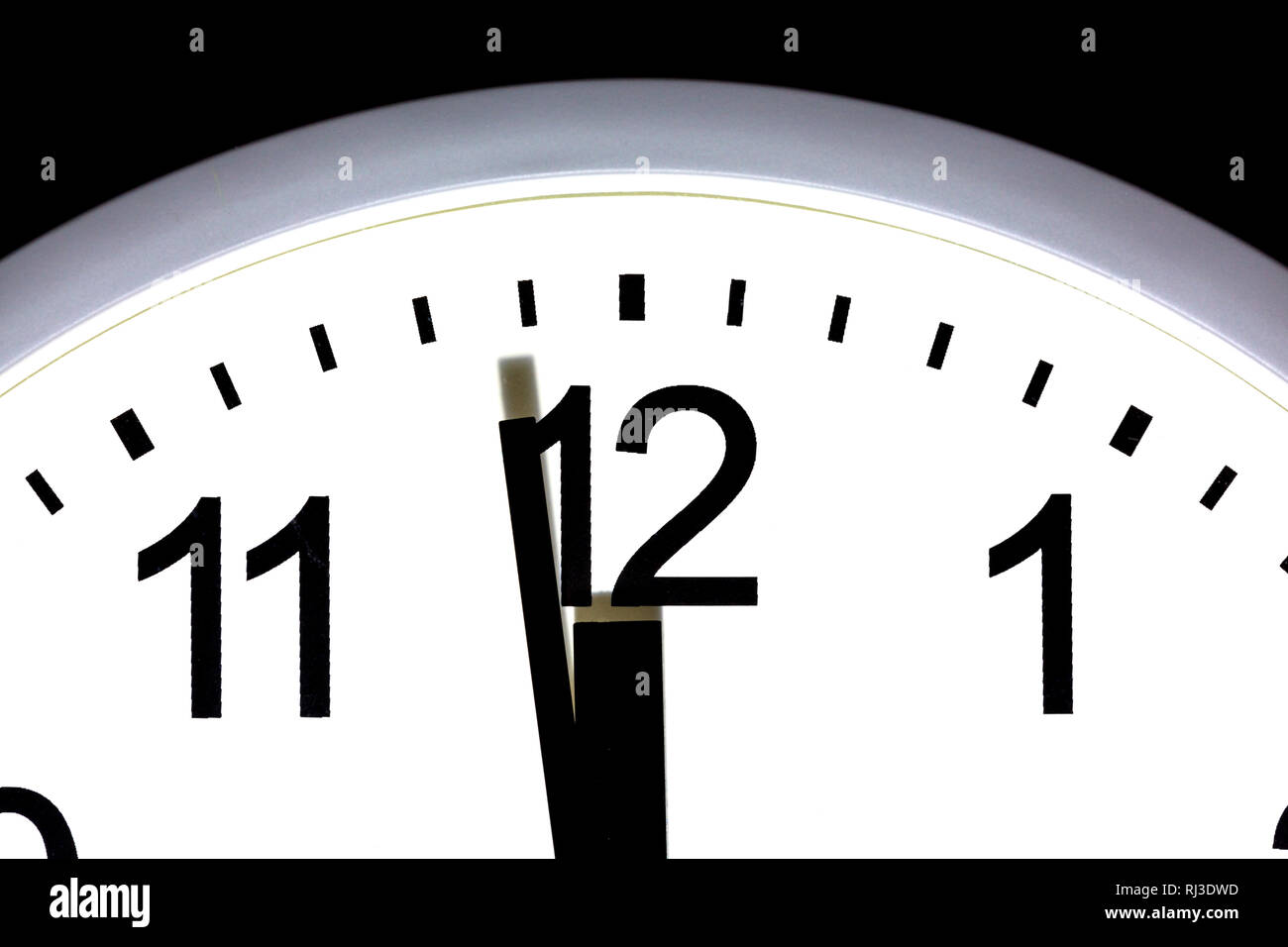 Close up of a clock showing one minute to 12, midnight. - Stock Image