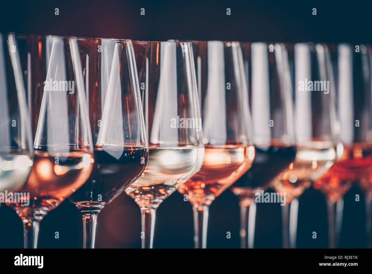 Wine glasses in a row. Buffet table celebration of wine tasting. Nightlife, celebration and entertainment concept. Horizontal, cold toned image Stock Photo