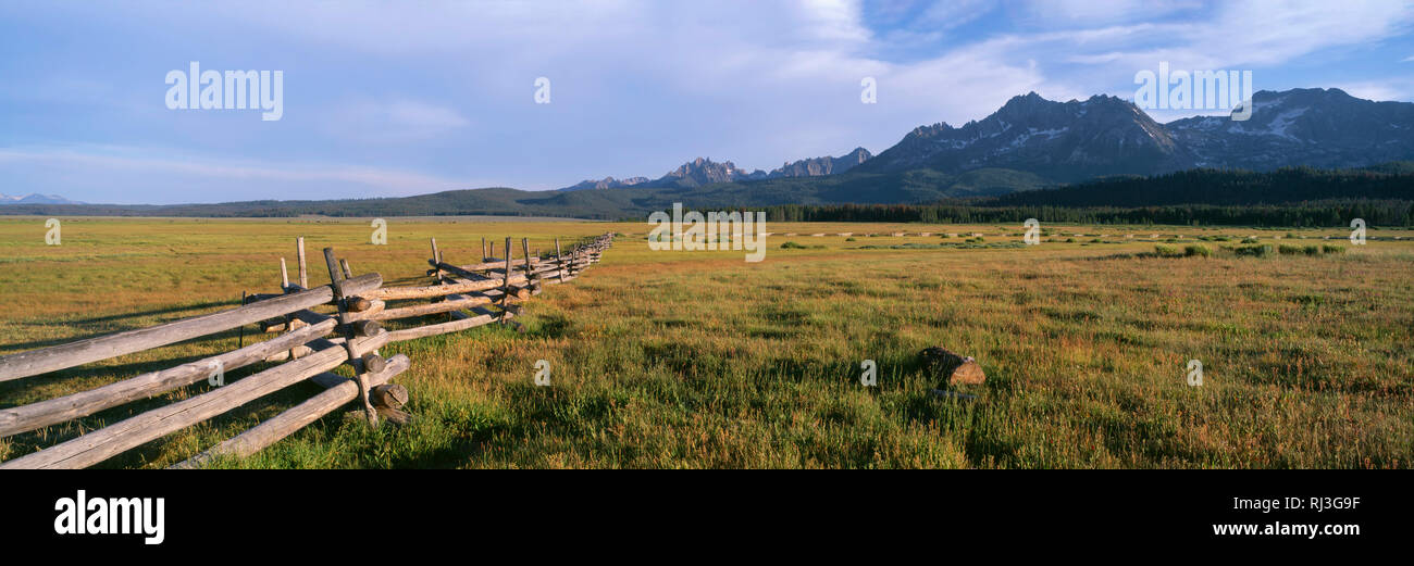 USA, Idaho, Sawtooth National Recreation Area, Sawtooth National Forest, Weathered fence crosses pastureland beneath forested hills and peaks of the S - Stock Image