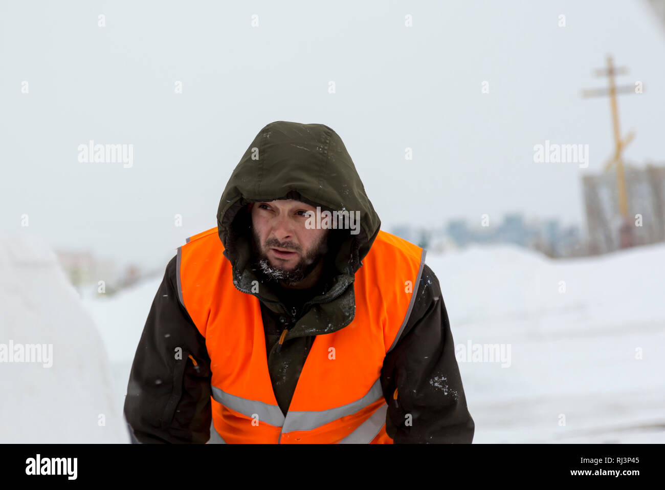 Portrait of installer in orange reflective vest - Stock Image