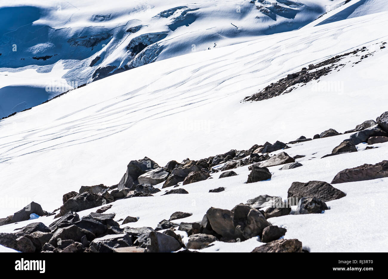 Melting snow revealing rocks on Mt. Rainier.  Ski tracks in the distance. - Stock Image