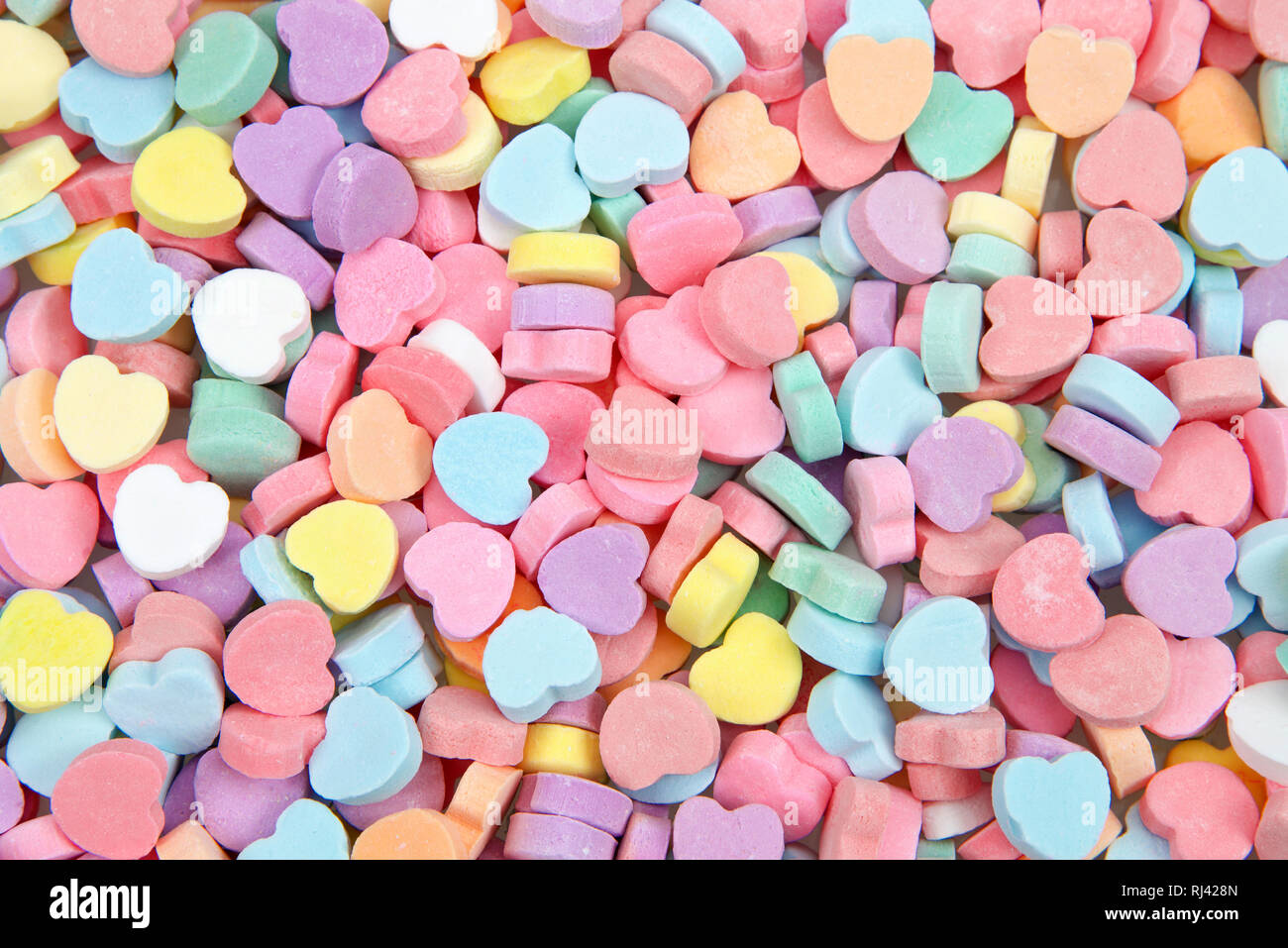 Background of brightly colored candy hearts for Valentine's Day. - Stock Image