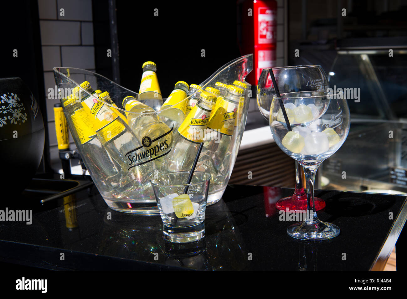 Key west, Fl, USA - March 30, 2016: Schweppes Tonic Water bottles yellow color in glass with cold ice cubes on table near bocals of lemon beverage with drinking straw - Stock Image