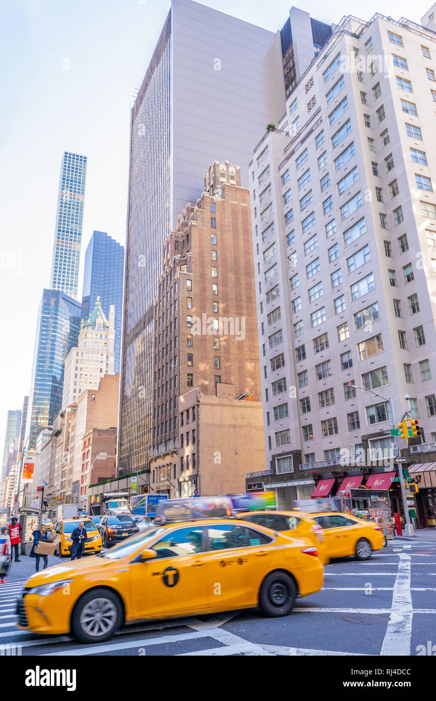 New York - October 17 2016: Yellow cabs, pedestrians and skyscrapers along the streets of Manhattan in New York City. - Stock Image