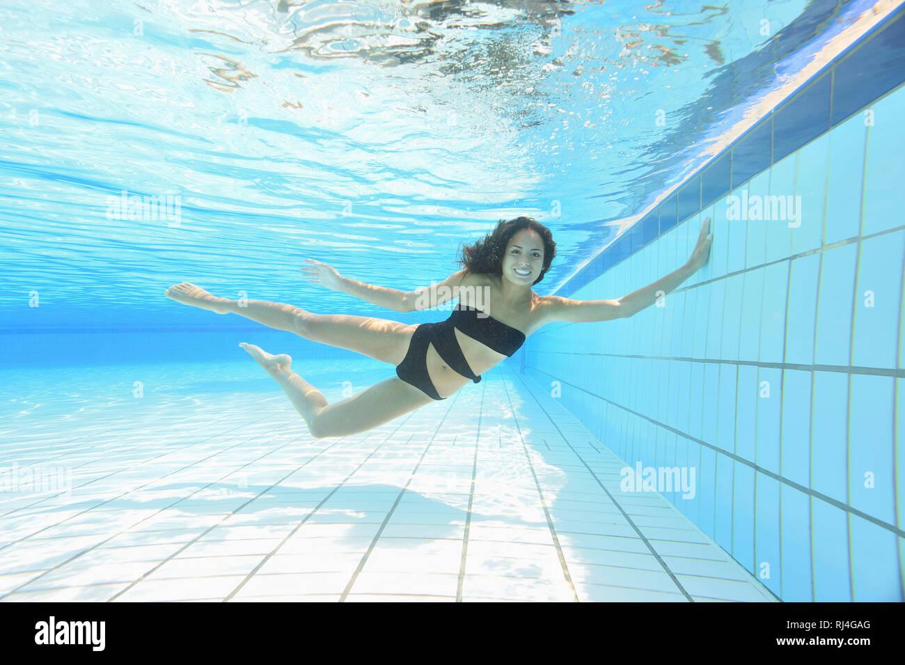 Frau, jung, Monokini, Freibad, Unterwasser, schwimmen, Blick Kamera - Stock Image