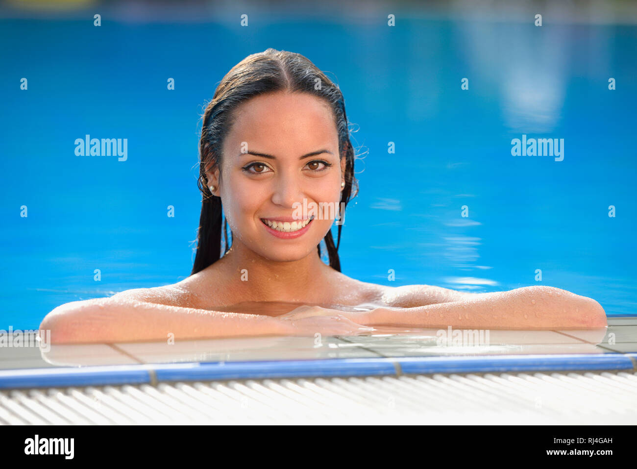 Frau, jung, Halbportrait, Bikini, Beckenrand, Freibad, frontal, Blick Kamera - Stock Image