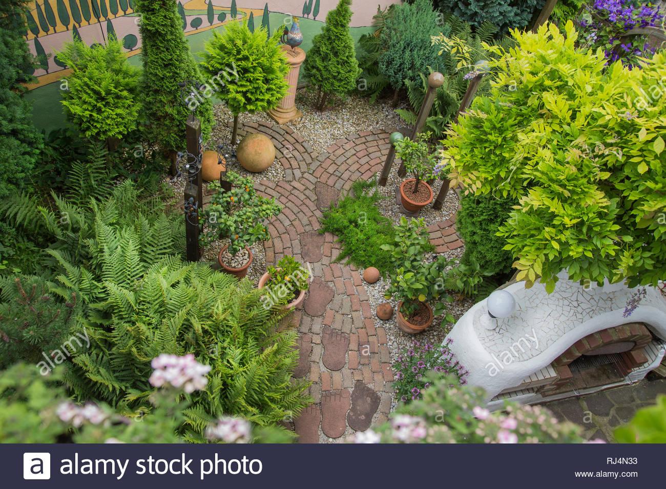 Gartenweg mit Rundungen, Grillkamin, bemalte Toskanalandschaft an Wand, Farne, Thujen, Dekoartikel, Pflaster, Fußabdrücke, von oben - Stock Image