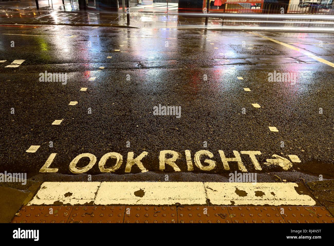 Straßenmarkierung auf einer regennassen Strasse, look right - Stock Image