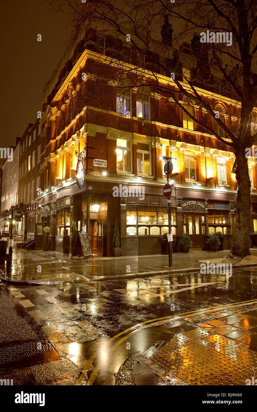 Der englische Pub the Fitzroy Tavern spiegelt sich in der nassen Straße - Stock Image