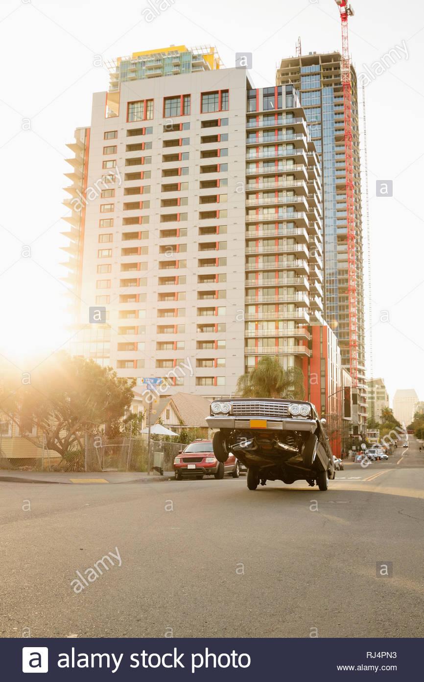 Low rider car bouncing on urban street - Stock Image