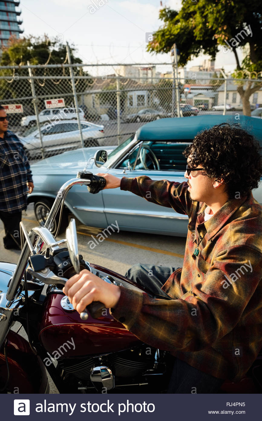 Latinx young man driving motorcycle - Stock Image