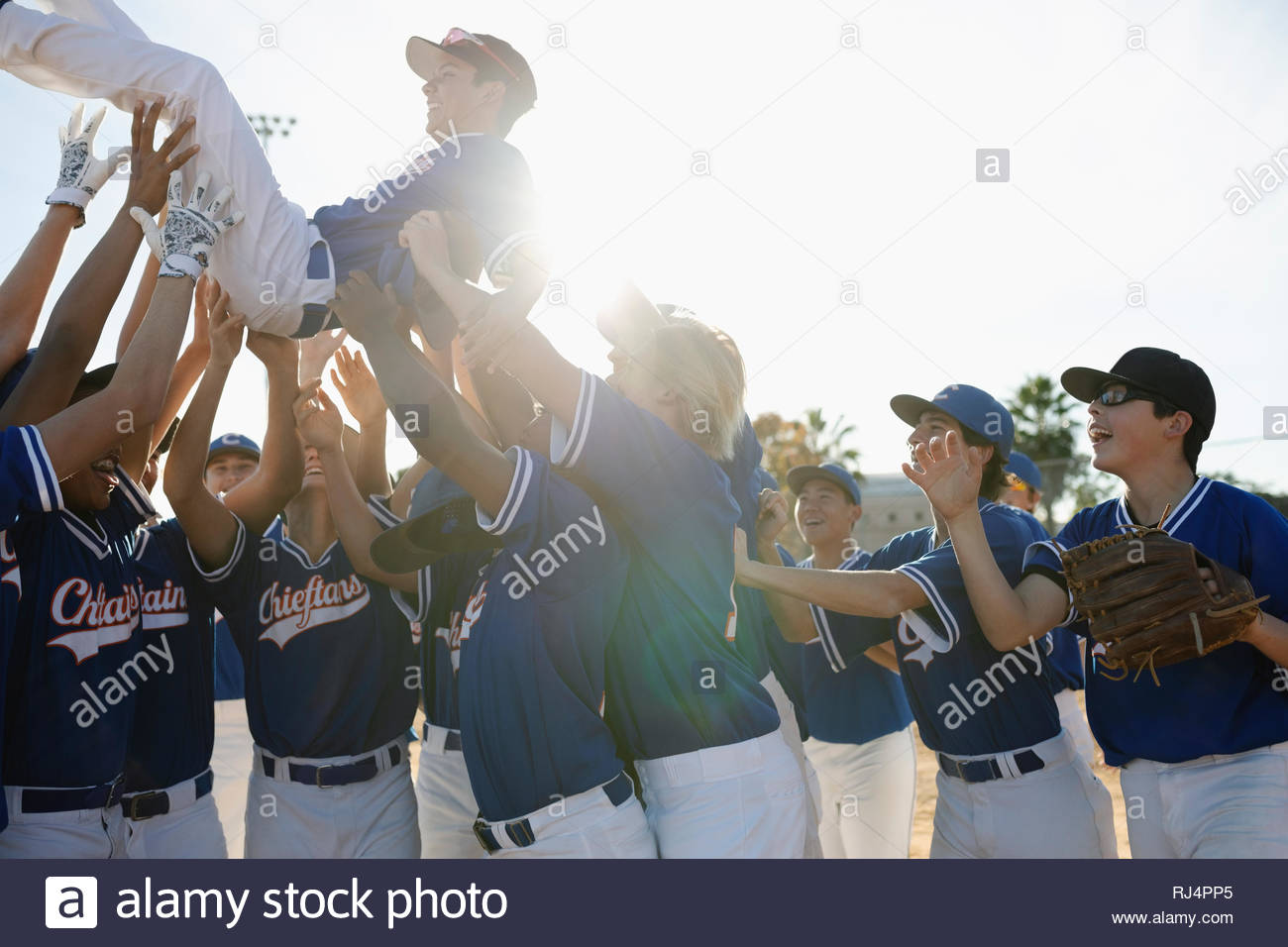 Happy baseball team celebrating, carrying player overhead Stock Photo