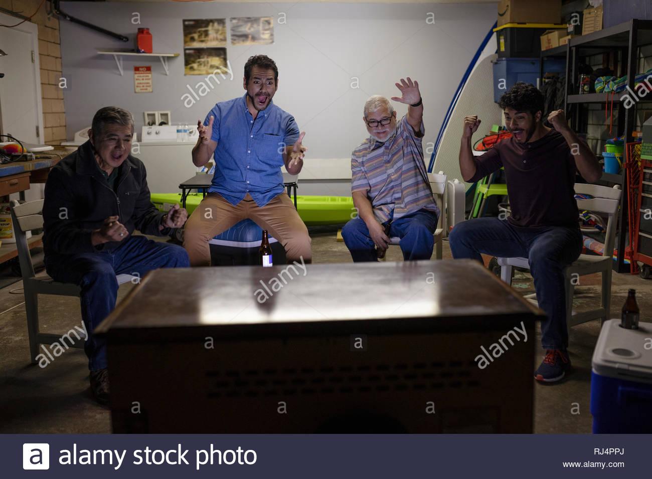 Latinx men watching sports on TV in garage - Stock Image