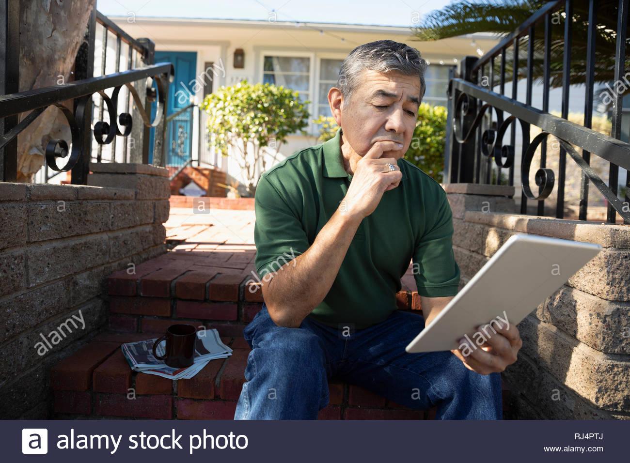 Latinx senior man using digital tablet on front stoop - Stock Image