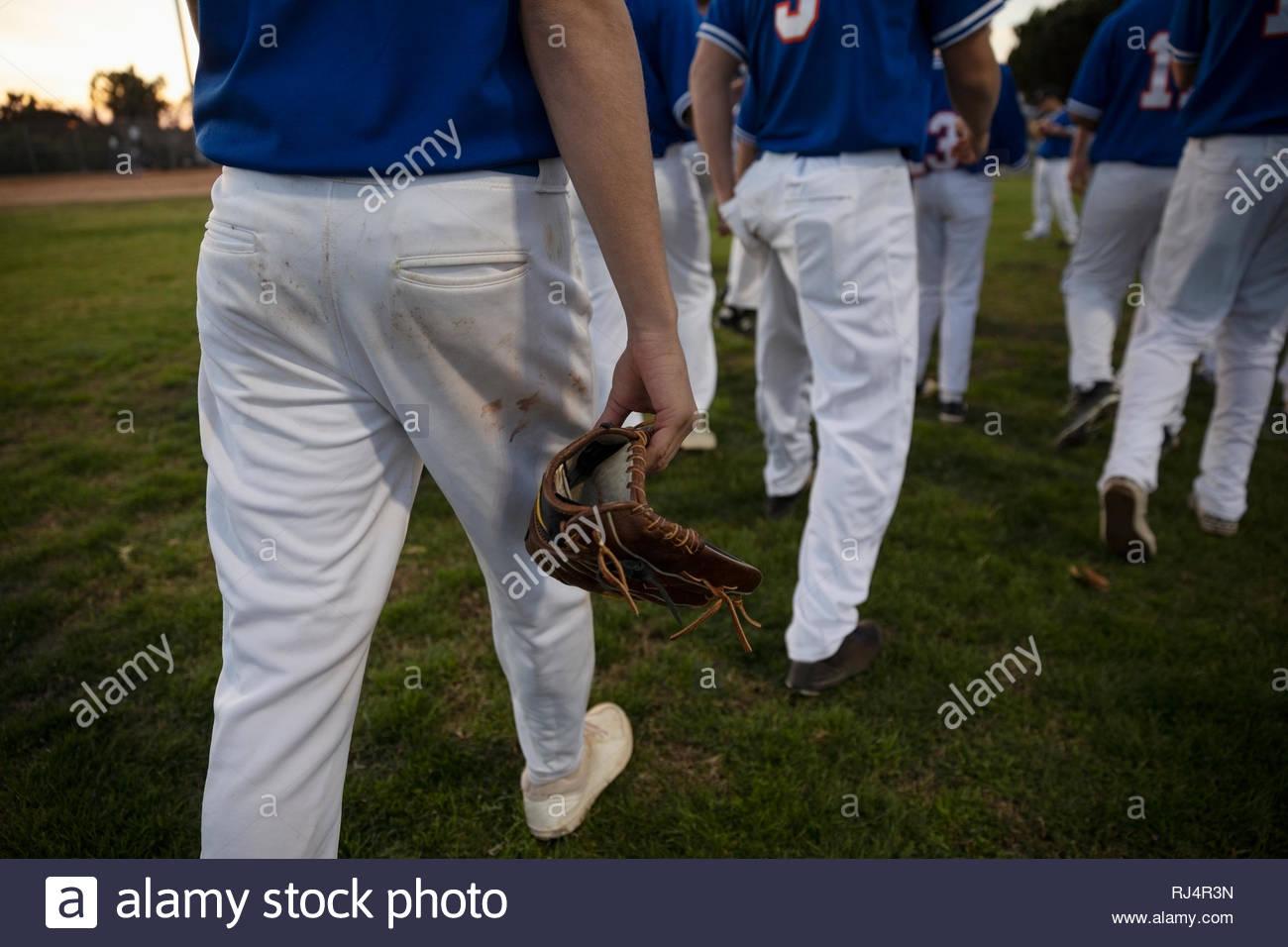 Baseball player with baseball glove walking on field - Stock Image