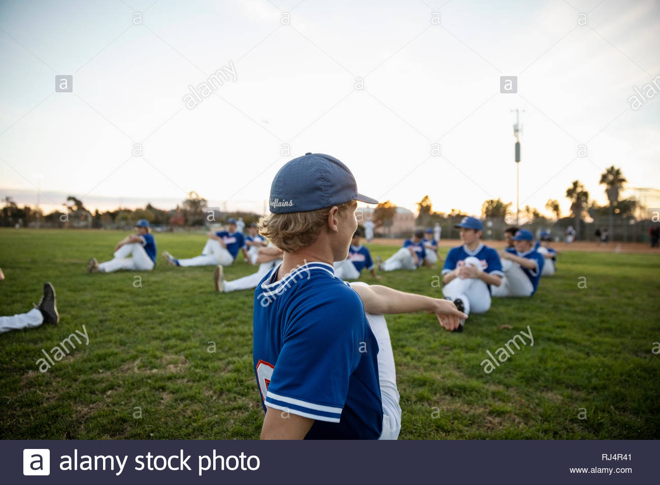 Baseball players stretching in grass - Stock Image