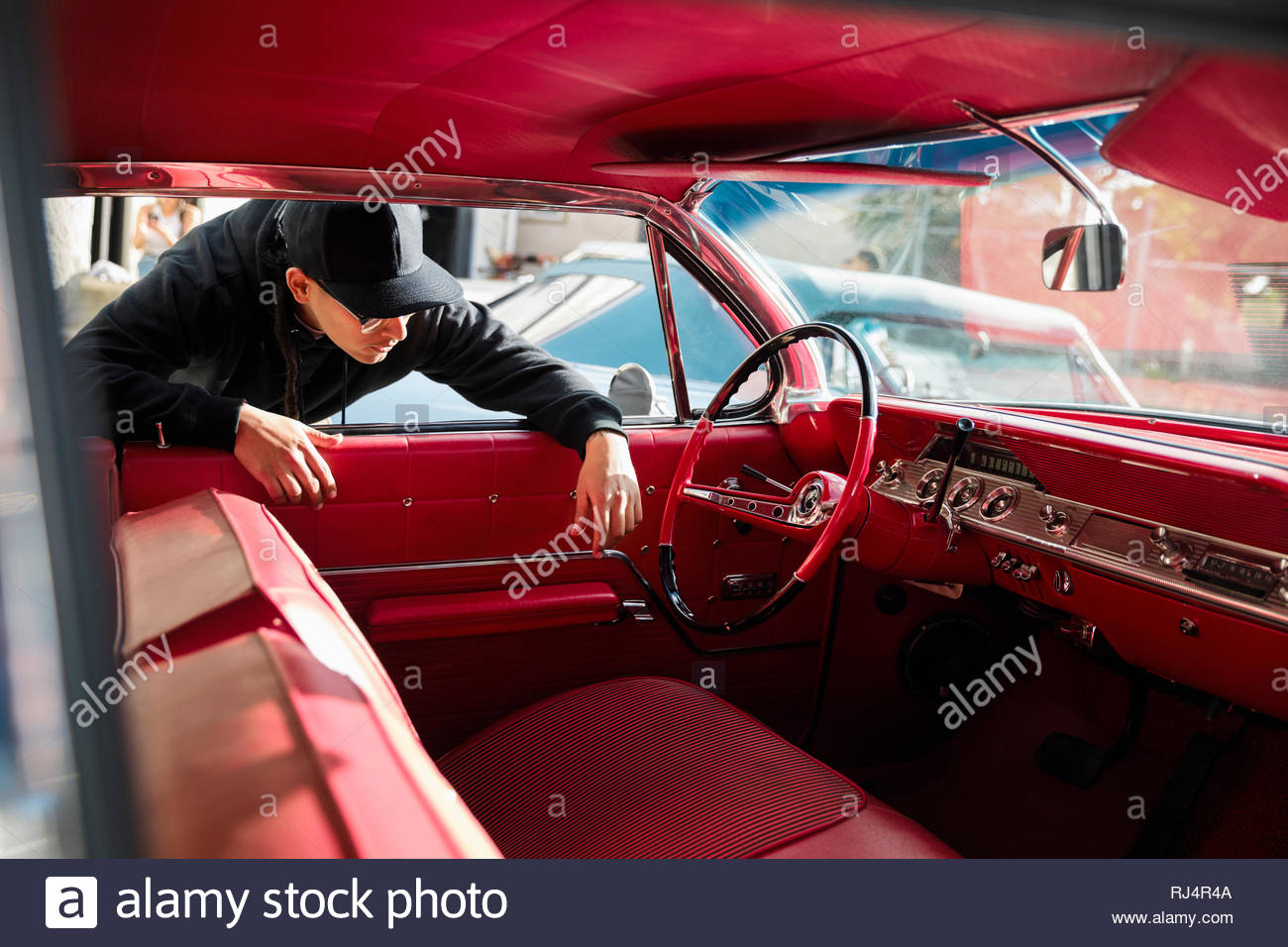 Latinx young man checking out red leather interior of vintage car - Stock Image