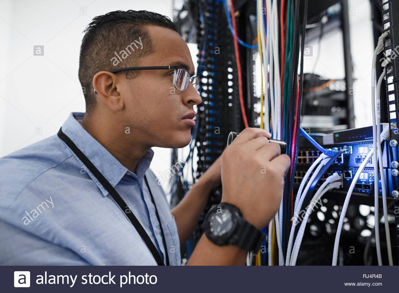 Focused IT technician examining connection plugs in server room - Stock Image