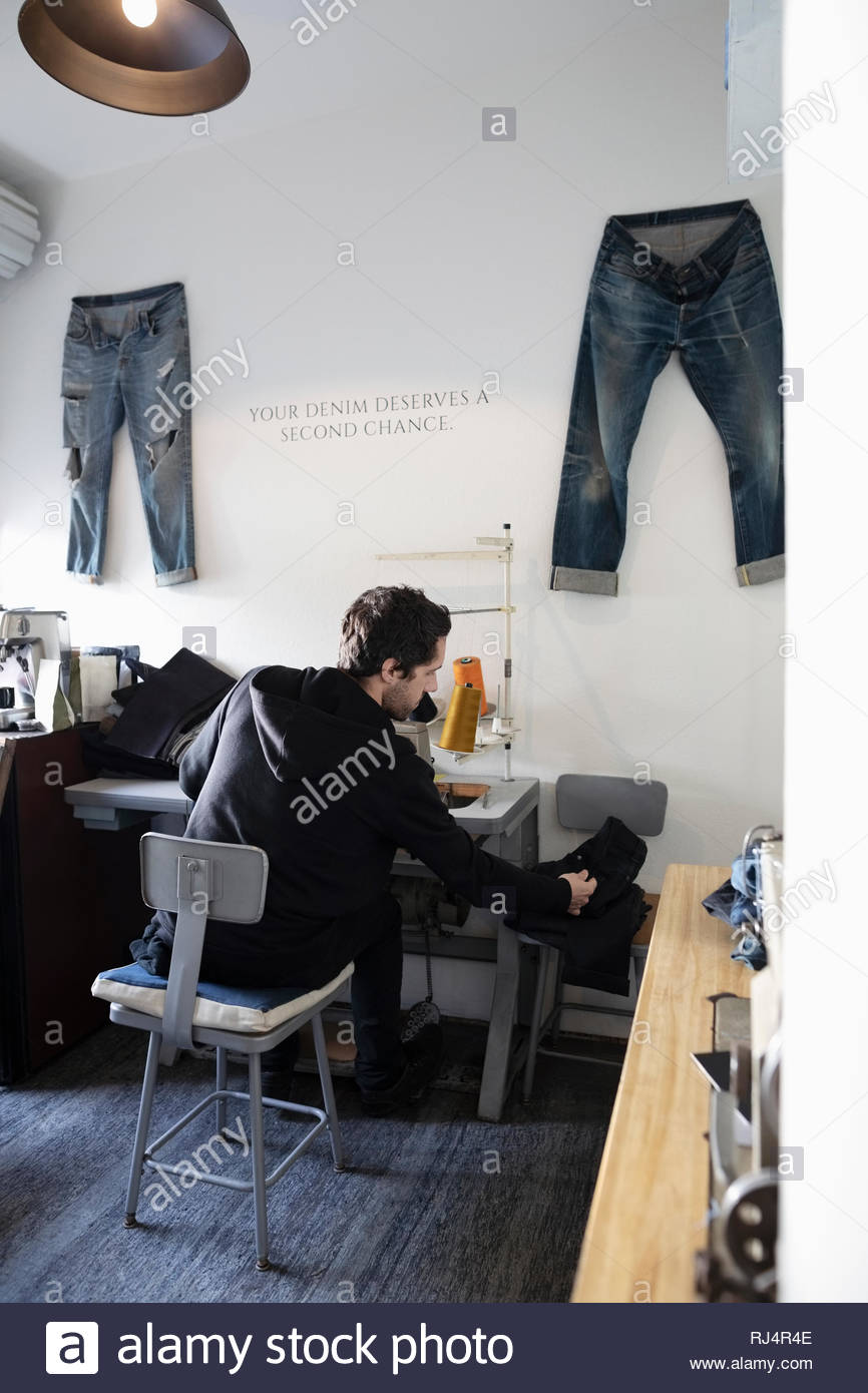 Male tailor working in denim repair shop - Stock Image