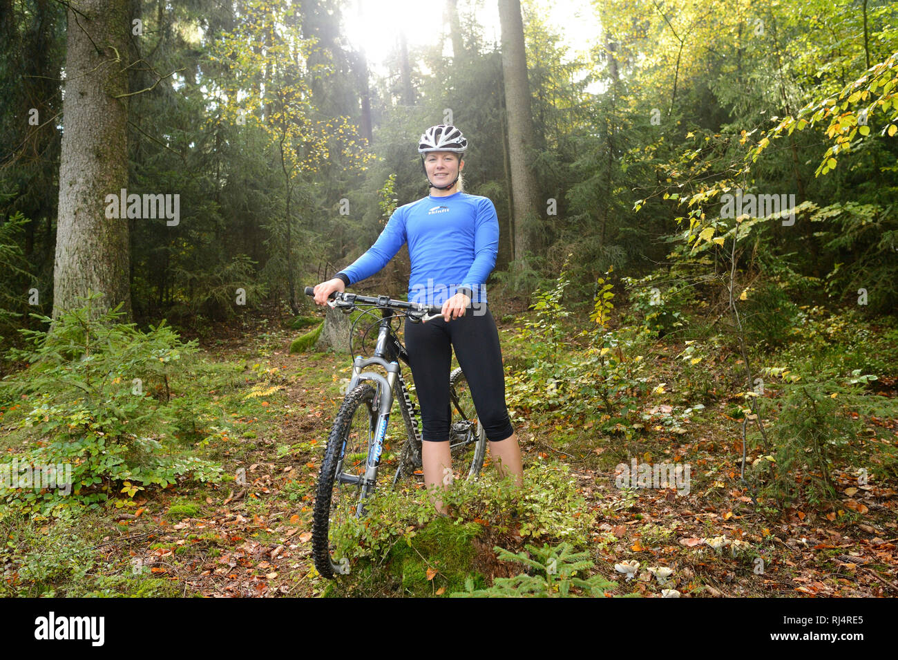 Frau steht mit Mountainbike im Wald, Blick Kamera, - Stock Image